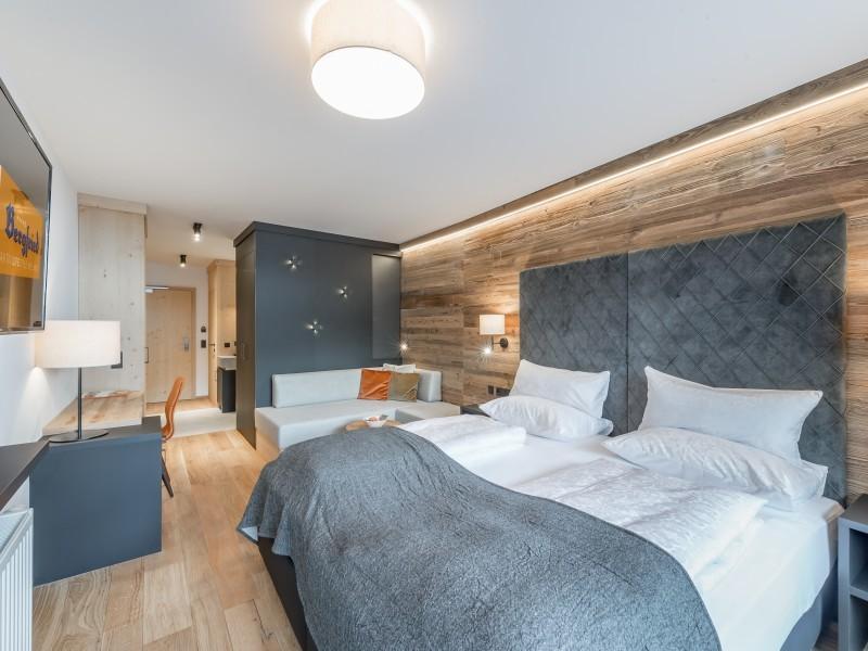 Doppelbett, TV, Schreibtisch und Couch in einem Zimmer