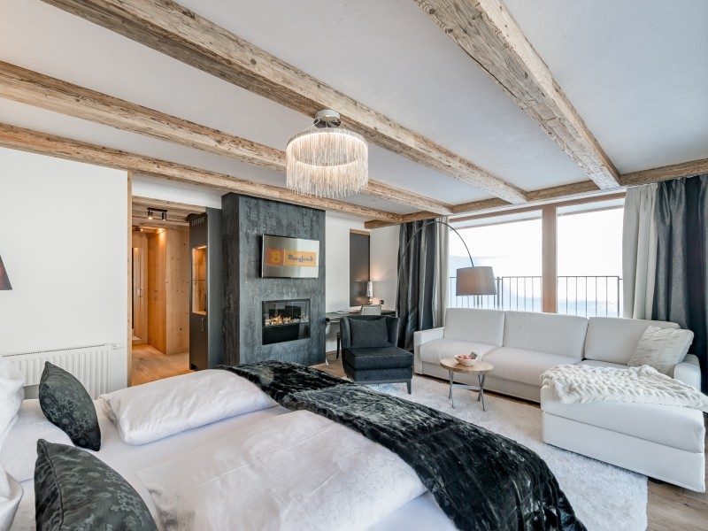 Sofa, Ofen und Doppelbett in einem Zimmer