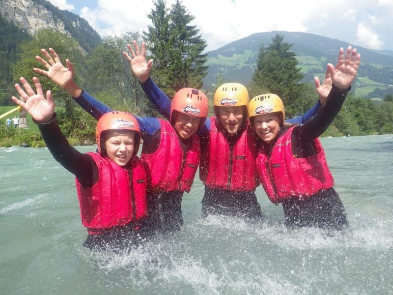 Vier Personen mit Helm und Schwimmweste im Wasser