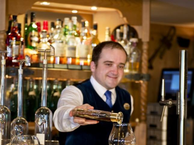Barkeeper schenkt Getränk in ein Weinglas