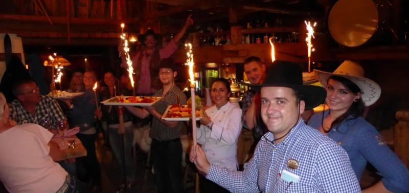 Menschen feiern in der Alm mit Essensplatten und Wunderkerzen